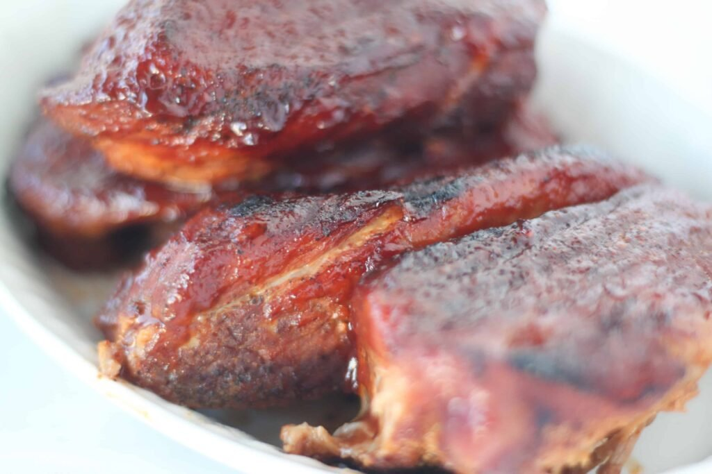 country style ribs pressure cooker recipe with a side angle photo of the ribs after adding more BBQ sauce