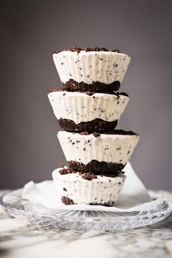 keto cany recipes like cookies and cream fat bombs stacked on top of each other on a gray background