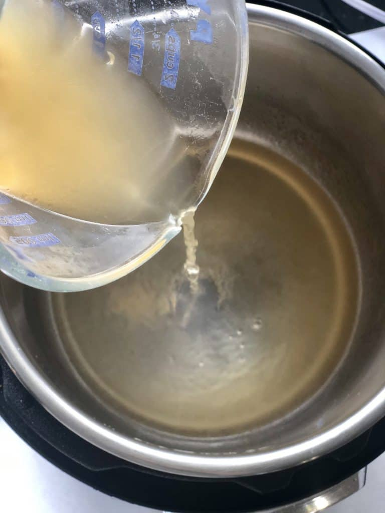 instant-pot-chicken tenders gets started by adding chicken broth to the pot