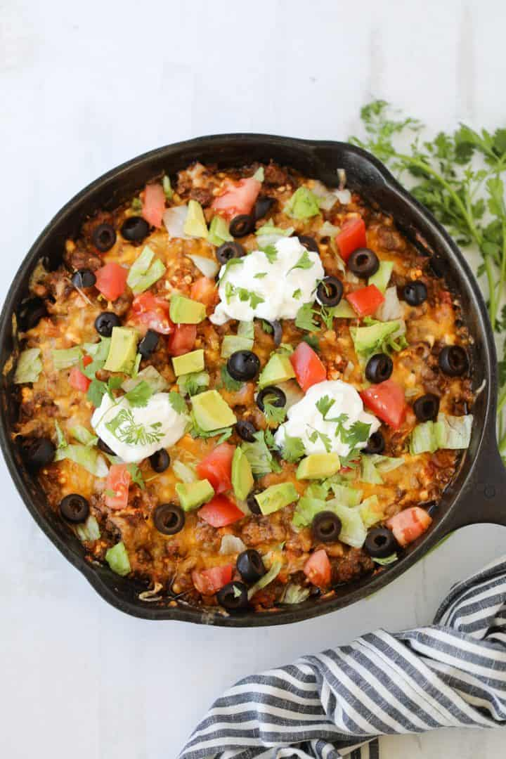 keto mexican casserole with taco toppings served in a cast iron skillet