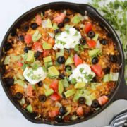 mexican taco casserole with garnishes in the pan