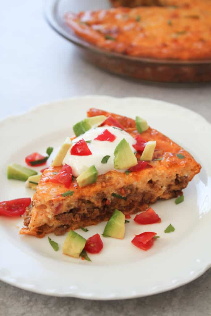 keto taco pie recipe on a plate with garnishes and the remaining pie in the background