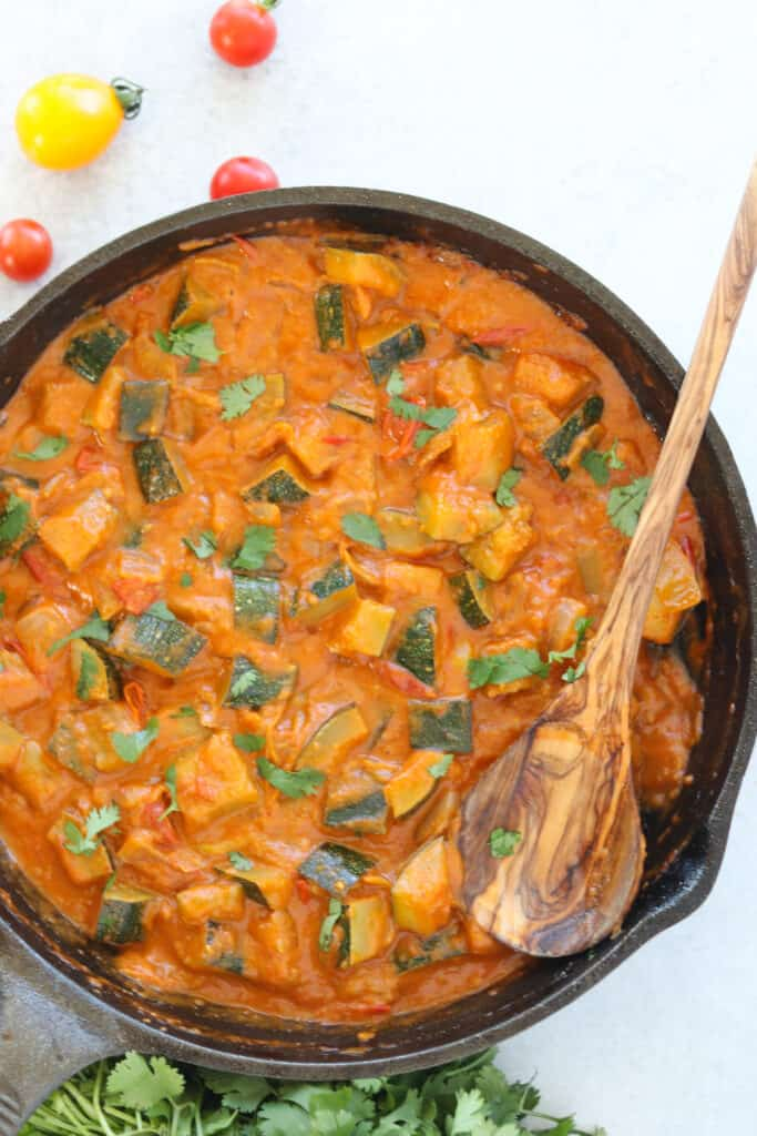 the zucchini curry in a pan after cooking top down view is also a thai red curry vegetarian recipe