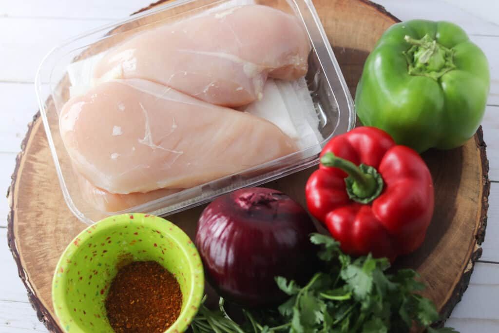 baked chicken fajita recipe ingredients on a cutting board