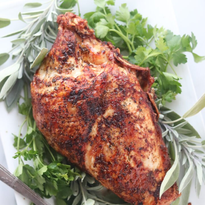 air fryer turkey breast cooked and surrounded with herbs