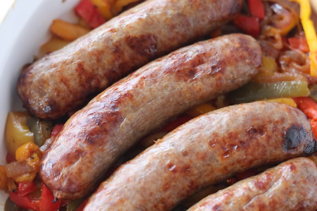 how to cook bratwurst without a grill, brats in a white dish on a bed of cooked peppers