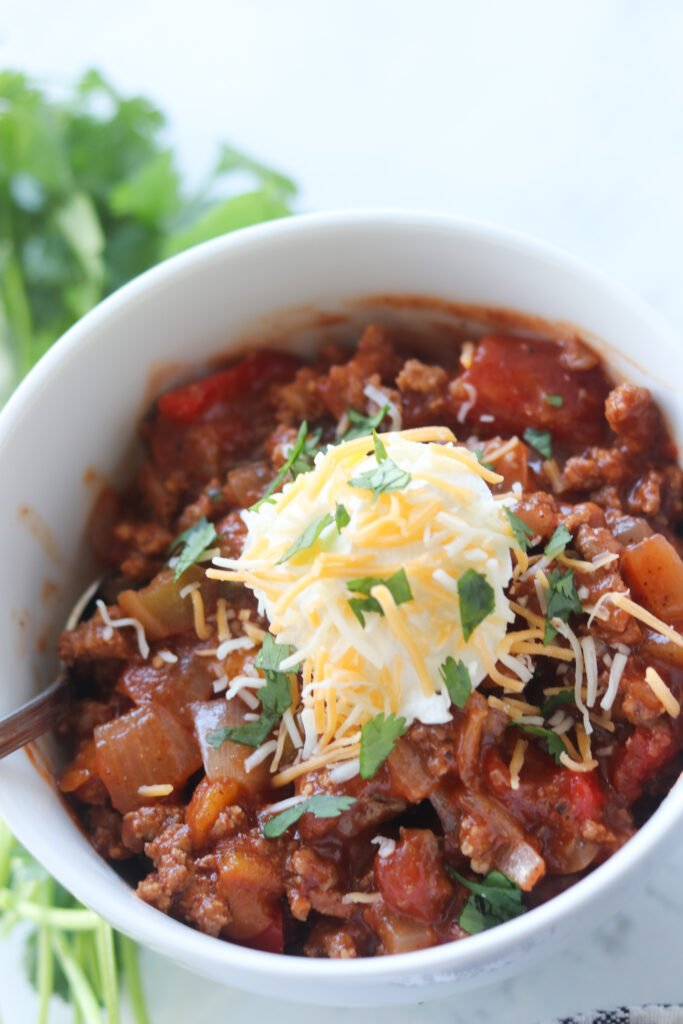 chili without beans in a white bowl with garnishes on top