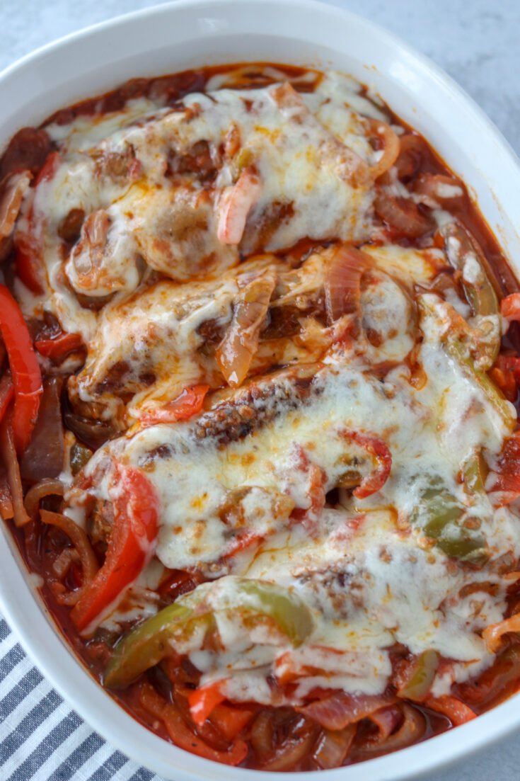 crockpot sausage peppers and onions with cheese in a white dish