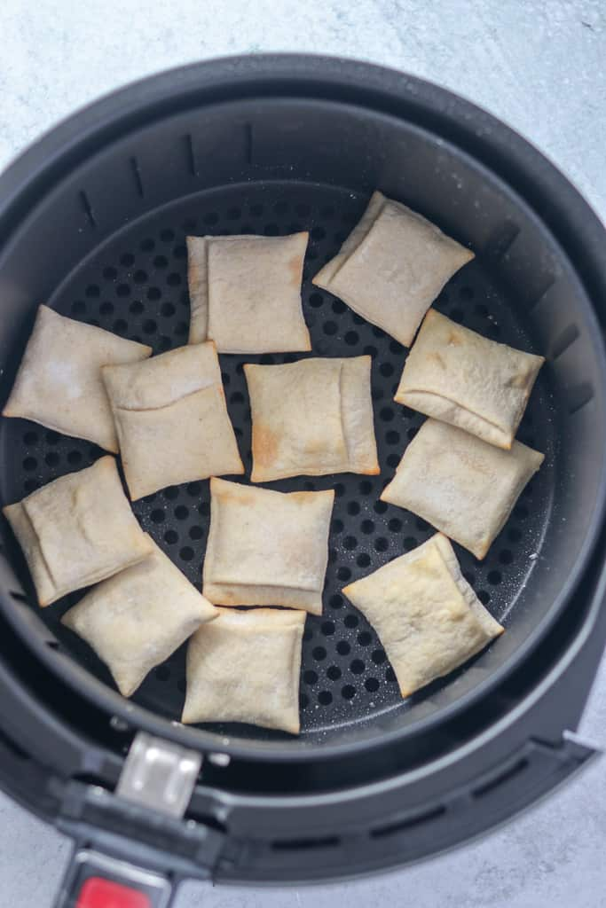 frozen air fryer pizza rolls being placed in a basket style model