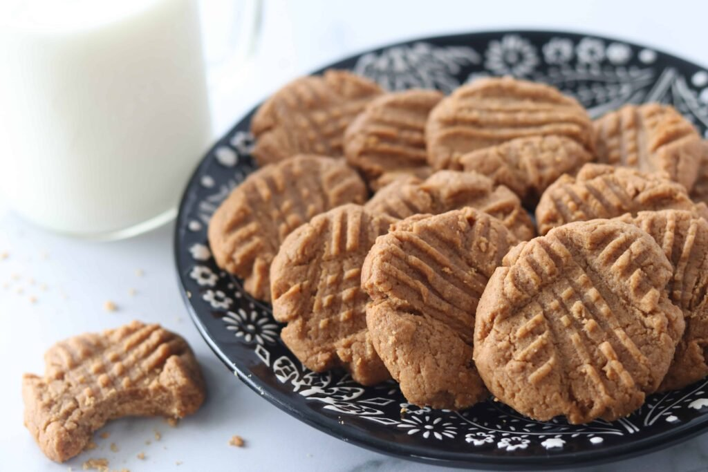 gluten free cookies on a black and white plate next to milk