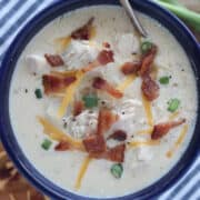 chicken bacon ranch soup in a blue bowl with garnishes