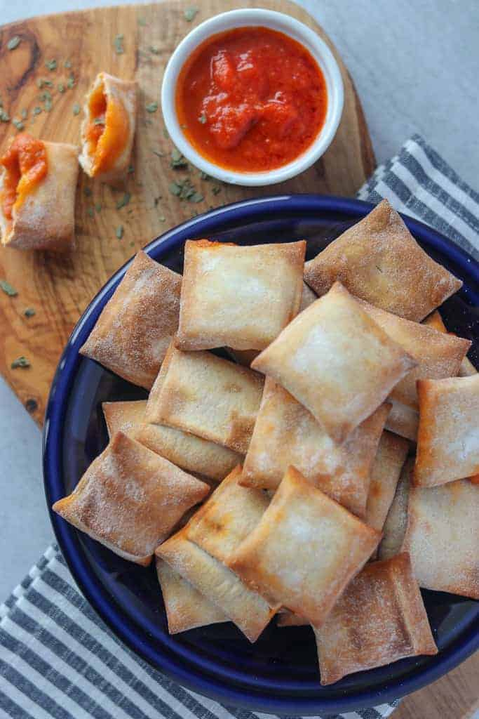 pizza rolls in air fryer on a blue plate with marinara sauce