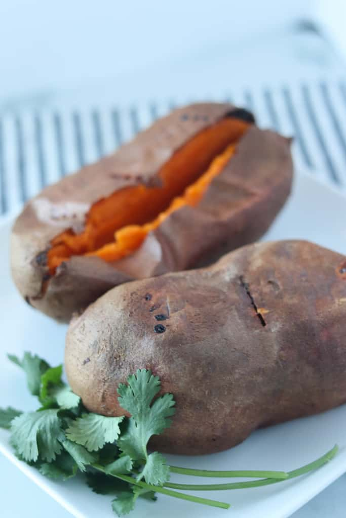baked sweet potato in air fryer after cooking sitting on a white plate