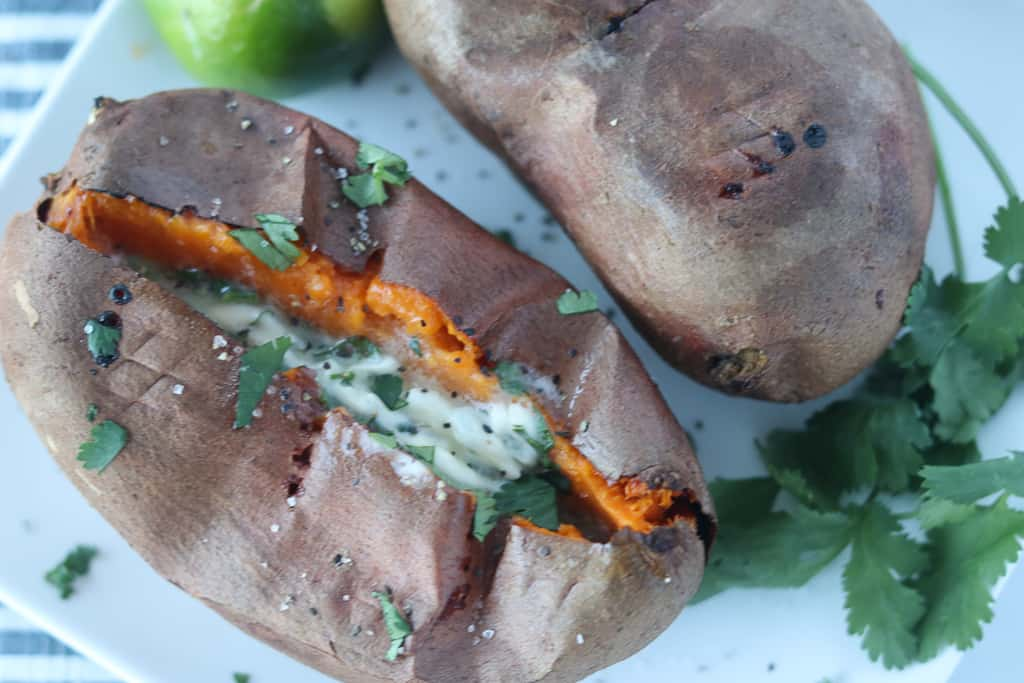 a roasted sweet potato air fryer variety on a plate cut open and fluffed with butter