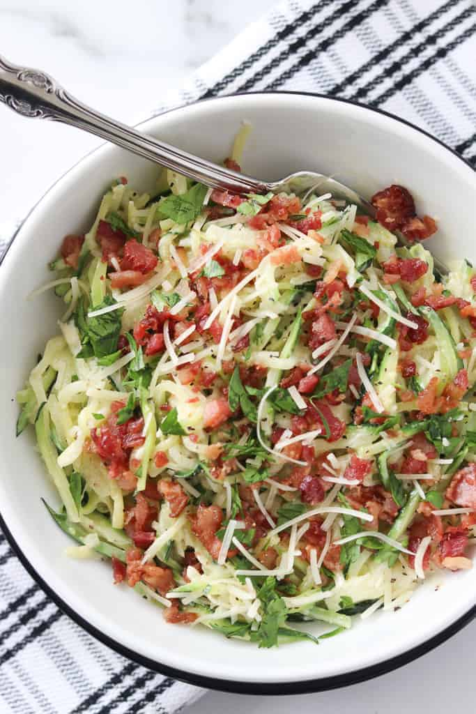 zoodle carbonara on a black and white background with a fork in the dish