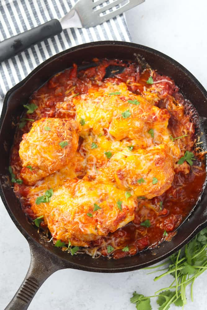 baked chicken with salsa in a skillet before serving