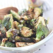 brussel sprouts in air fryer image after cooking in a clear glass bowl next to balsamic glaze