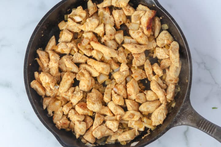 cooking chicken in a pan for keto enchilada bake