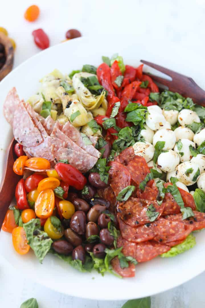 antipasto salad recipe in a serving bowl with salad tongs