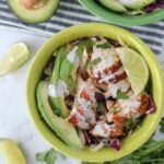 fish taco bowl with avocado and limes in a green bowl