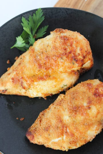air fryer chicken breast breaded on a black plate after cooking