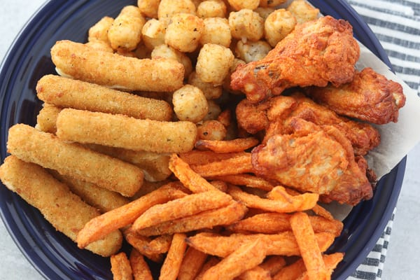 air fryer sweet potato fries frozen on a plate with other types of air fryer snacks
