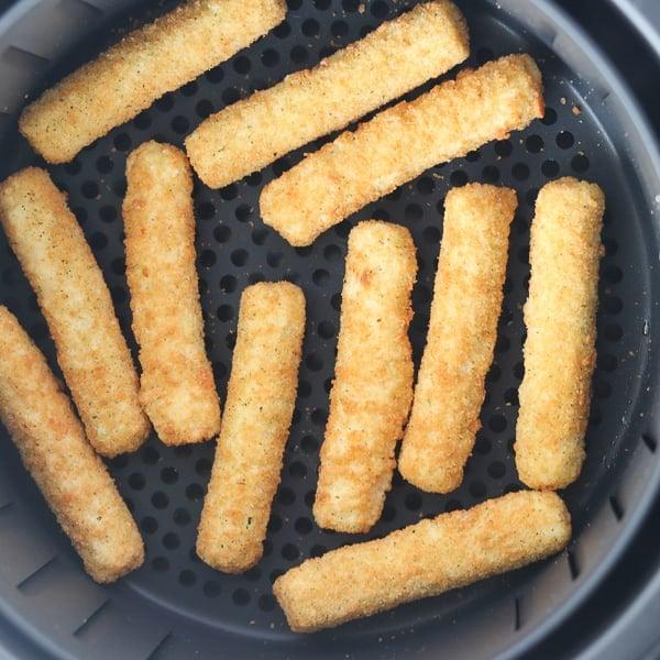 frozen mozzarella sticks in an air fryer basket ready to cook