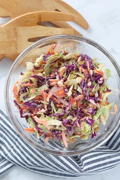 a healthy slaw recipe mixed in a bowl with serving tongs