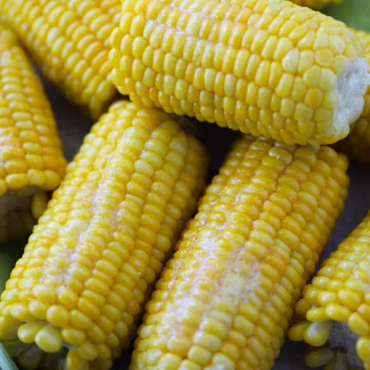 how to cook frozen corn on the cob is the same as fresh corn. Showing finished corn with butter up close after cooking.