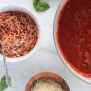 low carb spaghetti sauce in a pot next to keto pasta noodles and cheese