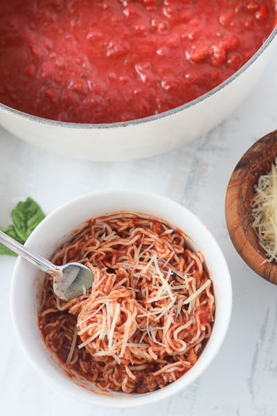 low carb spaghetti in a bowl with a pot of sauce on the side