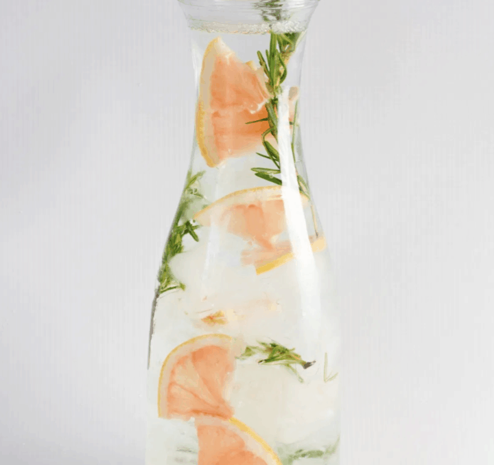 fruit infused water recipes like this grapefriut and rosemary in a tall narrow pitcher