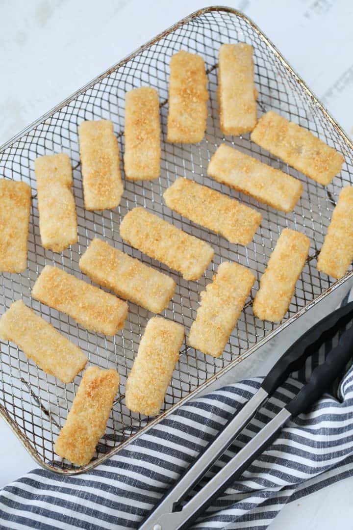 air fryer frozen fish sticks spread out on a pan before cooking