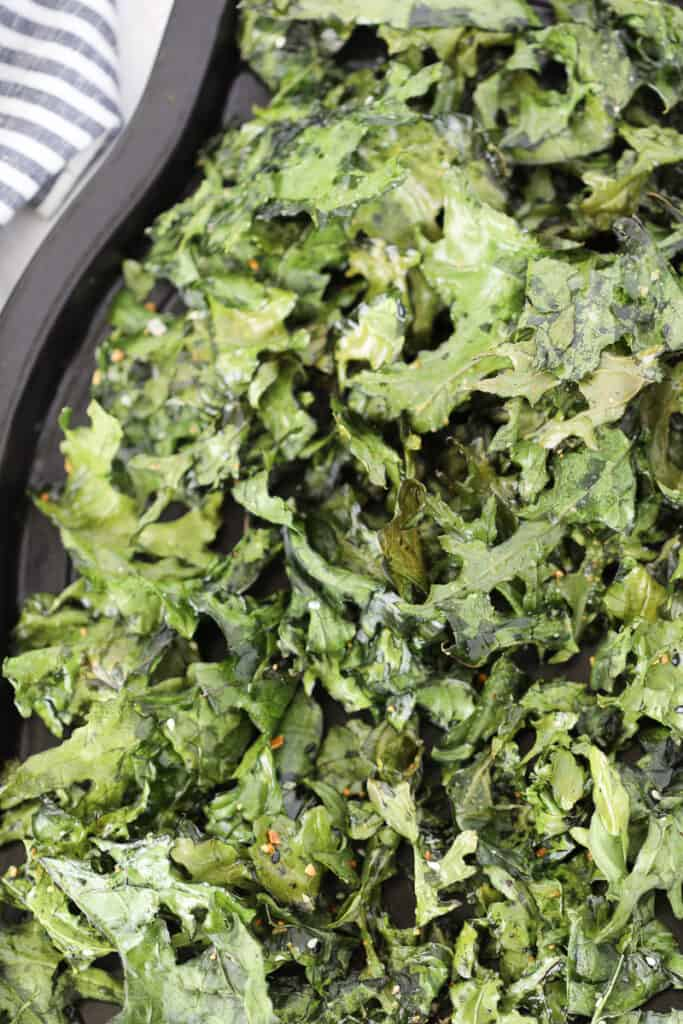 multiple batches of air fryer kale chips on a baking tray