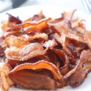 cooking bacon in air fryer on a white plate after it's done