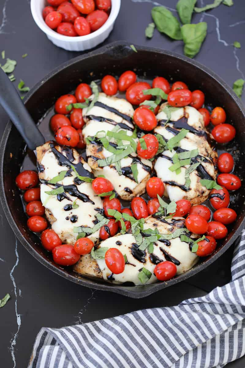 baked caprese chicken recipe after cooking drizzled with balsamic glaze and sprinkled with fresh basil