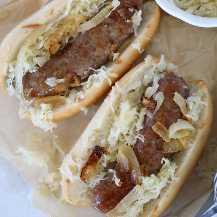 cooking brats in the oven served on buns with sauerkraut and onions