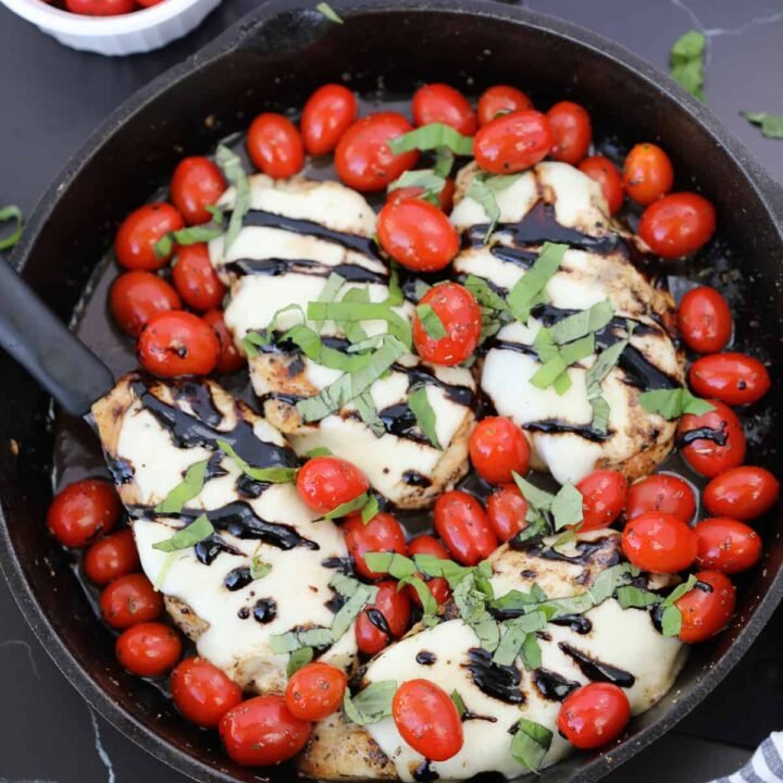 caprese chicken bake in a cast iron skillet with balsamic glaze