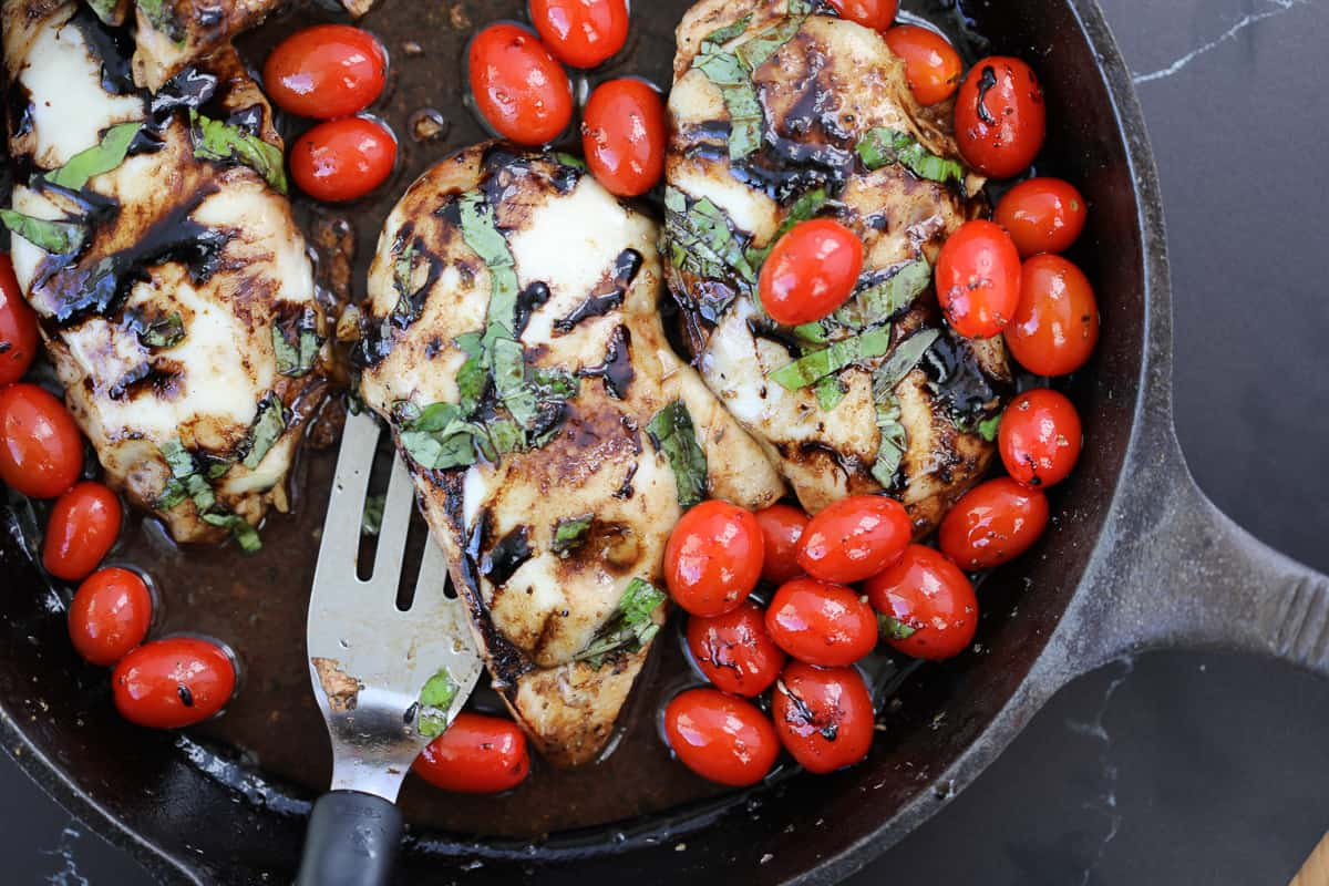 caprese chicken in a cast iron skillet with pan sauce drizzled over the top