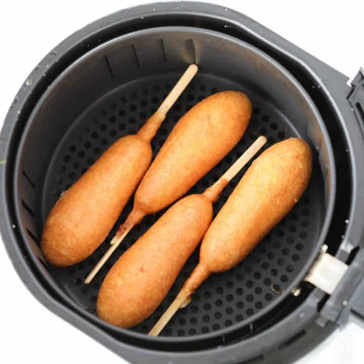 frozen corn dogs in air fryer basket ready to be cooked