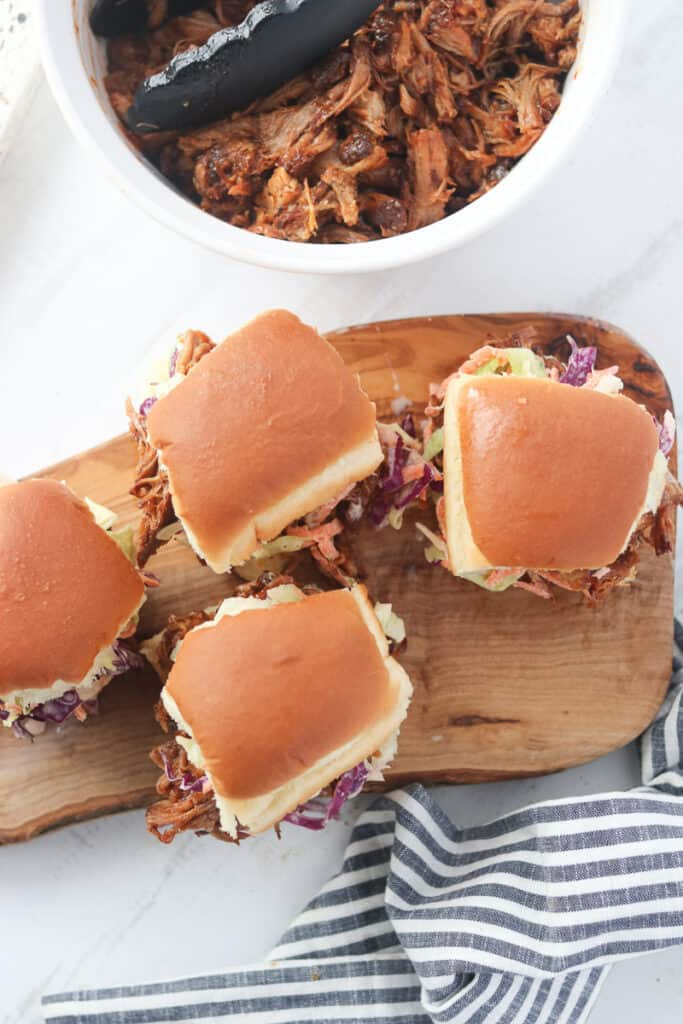 hawaiian pulled pork sliders top down view with the sliders on a cutting board next to a bowl of pulled pork