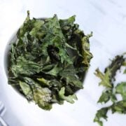kale chips in air fryer recipe after cooking displayed in a white bowl