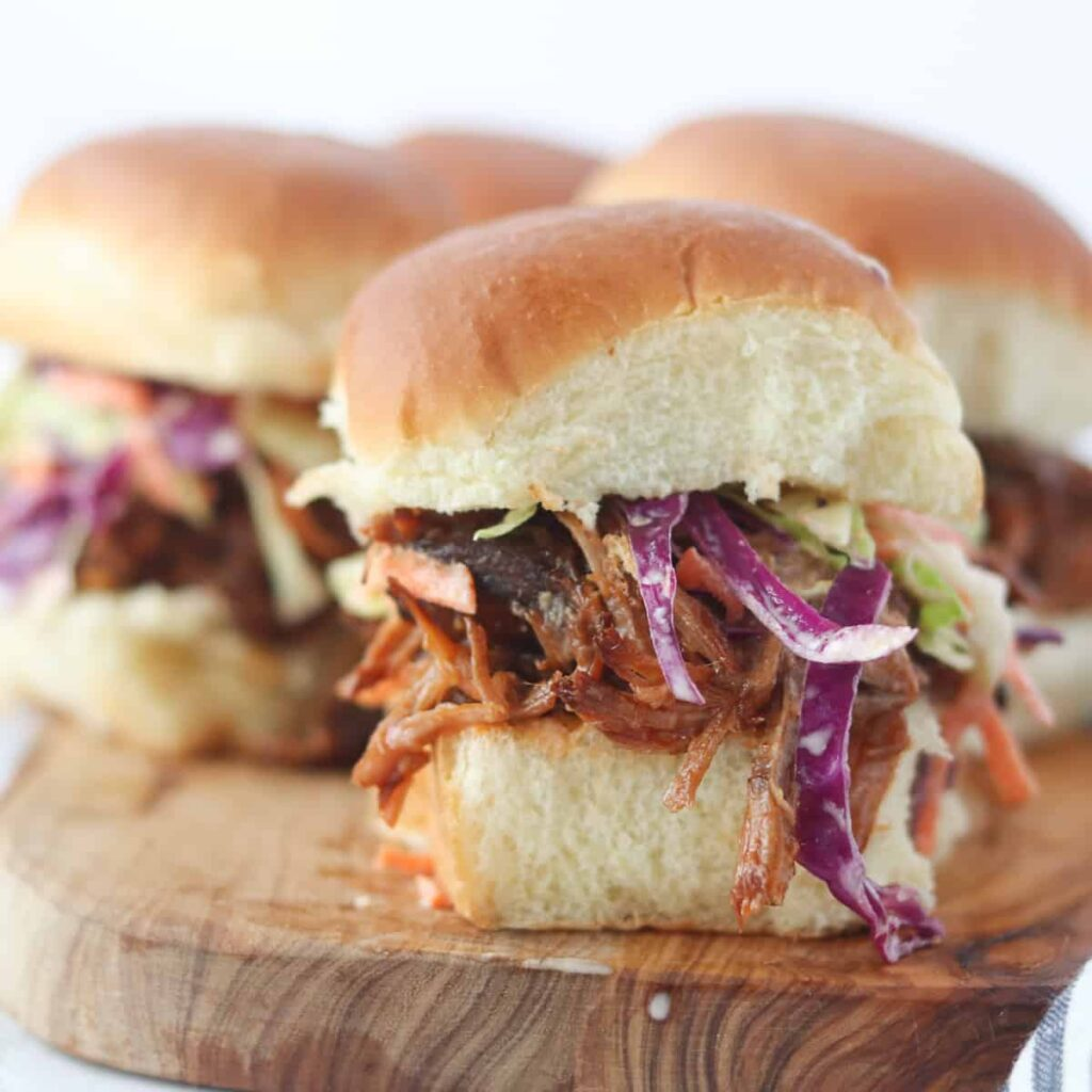pulled pork sliders on hawaiian rolls displayed on a cutting board