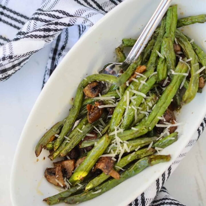 air fryer green bean with mushroom recipe in a white bowl sprinkled with parmesan