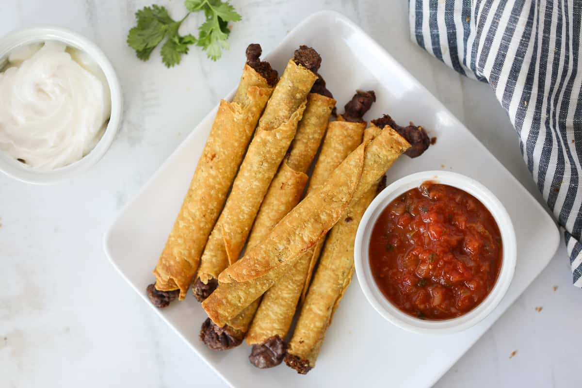 cooking air fryer taquitos frozen is an easy snack or dinner served with salsa and sour cream.