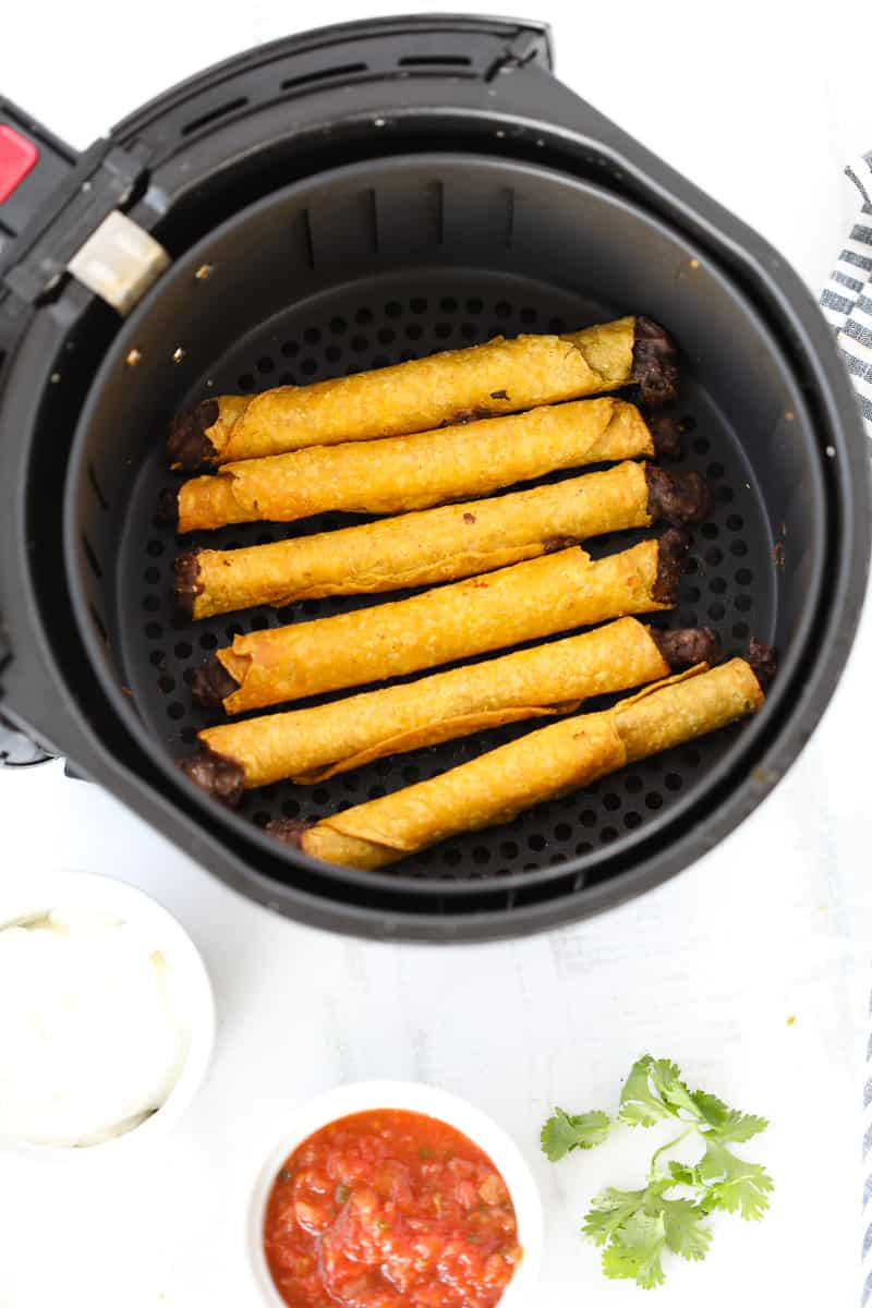air fryer taquitos in a farberware basket style air fryer after cooking with salsa and sour cream in dishes on the side