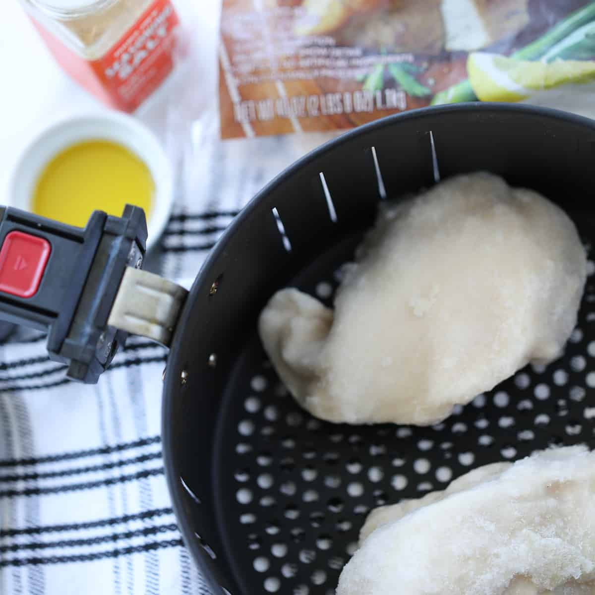 cooking frozen chicken breast in air fryer uses raw meat, olive oil, and seasoning. Photo is of all ingredients before cooking.