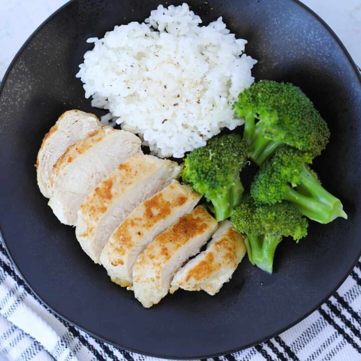 frozen chicken breast air fryer recipe after cooking served sliced on a plate with broccoli and rice