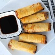 frozen egg rolls in air fryer on a white plate with soy sauce