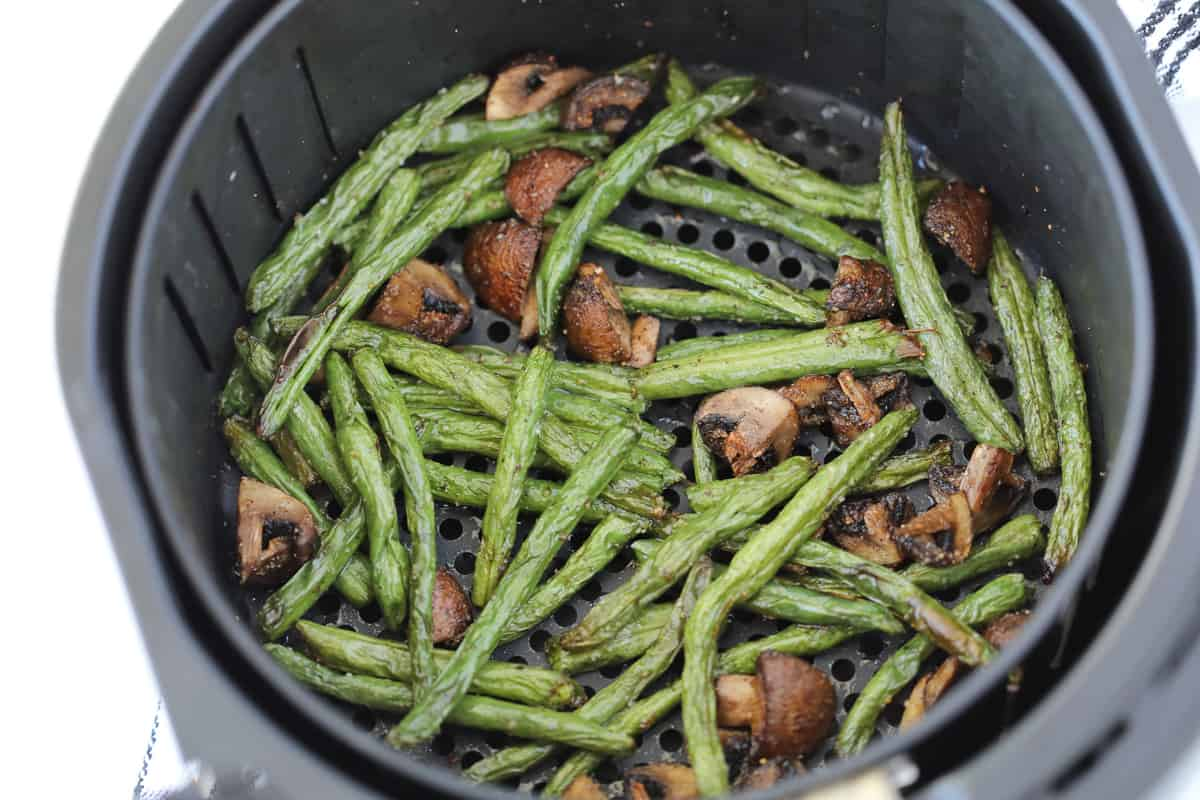 green beans in air fryer basket with mushrooms right after getting cooked